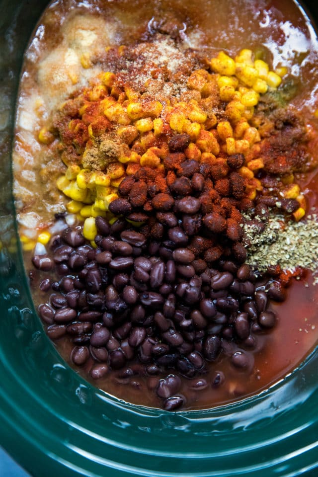 adding all ingredients to a crockpot for tortilla soup