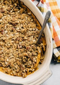 sweet potato casserole in a white dish with a large serving spoon