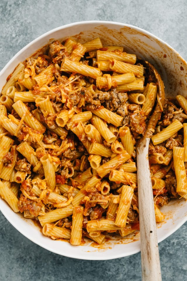 stirring ingredients for baked ziti together in a large pot