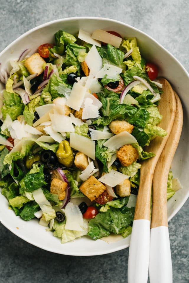 an Italian salad in a large white bowl with salad tongs