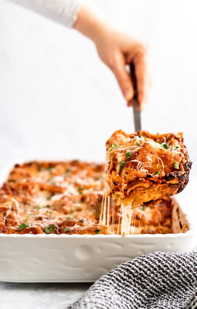 woman's hand scooping a serving of lasagna out of a large white dish