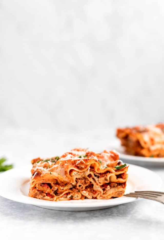 serving of lasagna on a white plate with a fork