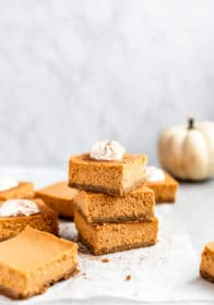 pumpkin cheesecake bars stacked and topped with whipped cream
