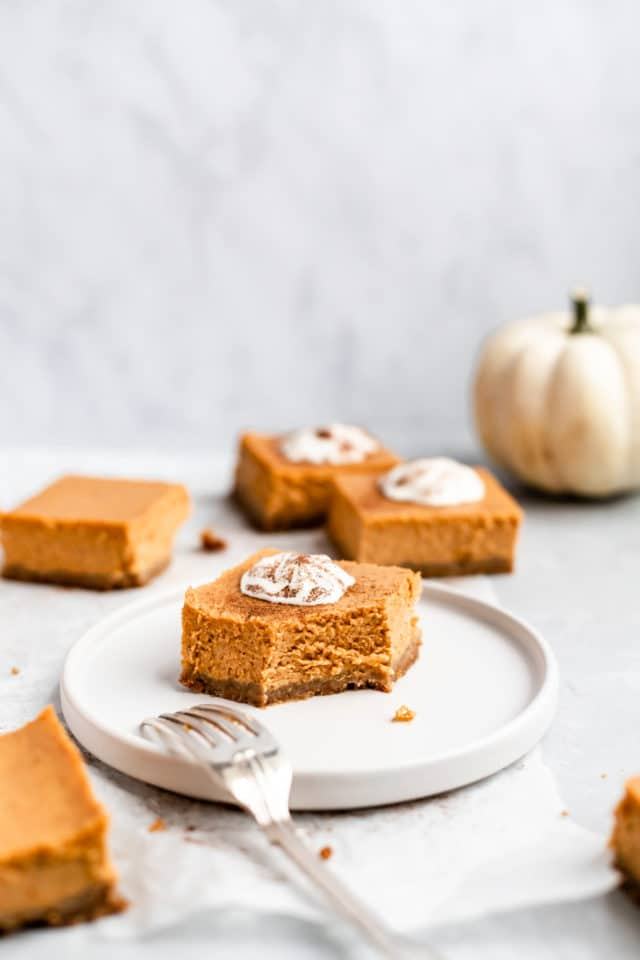 pumpkin cheesecake bar served with whipped cream on a white plate