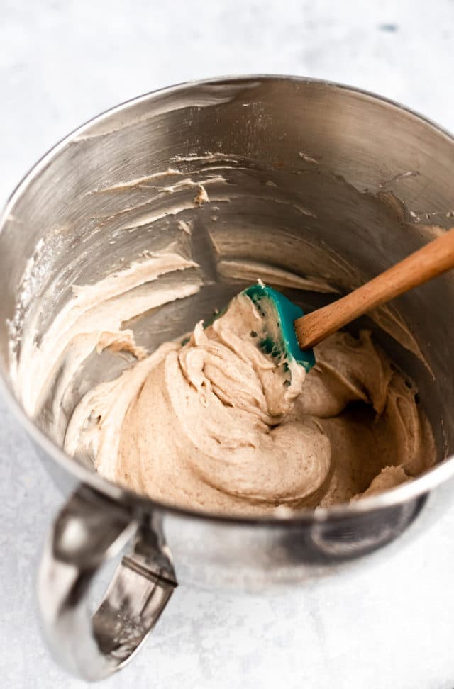 Cream cheese frosting mixed in a silver mixing bowl for pumpkin cupcakes