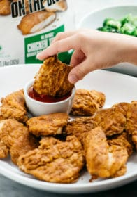 child's hand dipping a Healthy Baked Chicken Tenders into ketchup