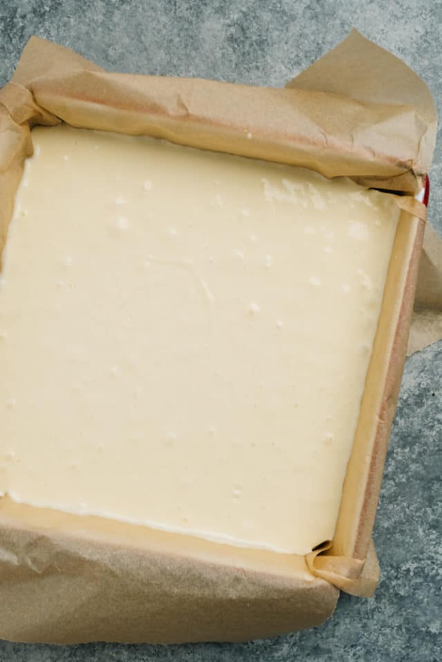 pour cheesecake filling over graham cracker crust in baking pan