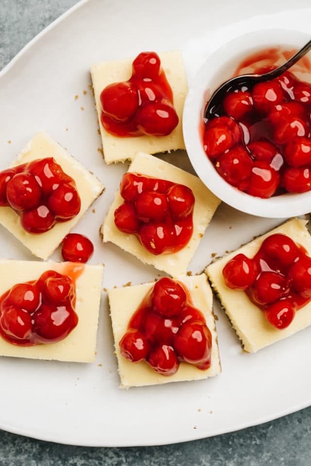 cherry cheesecake bars served on a large white serving dish