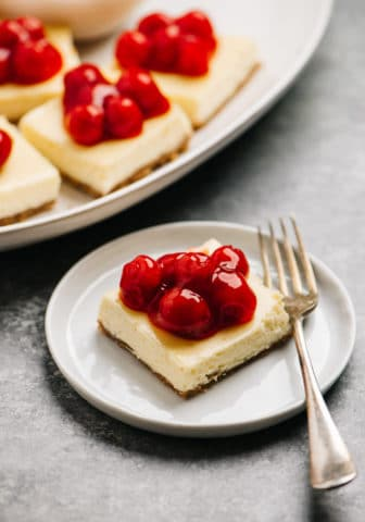 cheesecake bars on a white plate topped with cherries