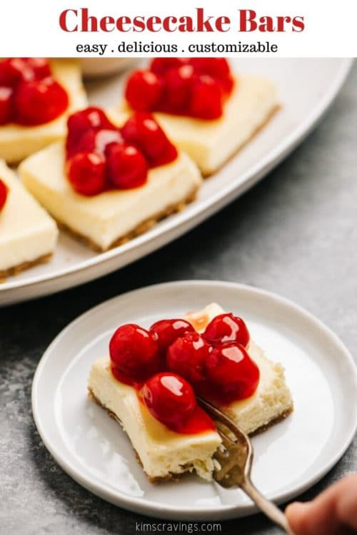 cheesecake bars served on a white plate with a fork taking a bite