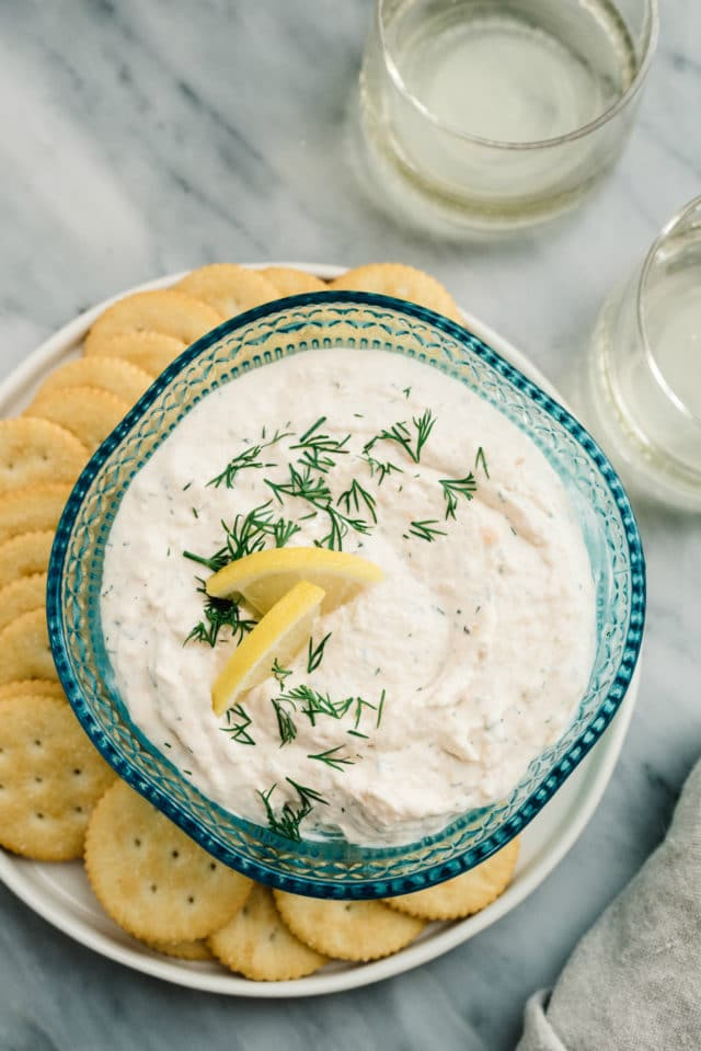 smoked salmon dip served in a blue bowl with Ritz crackers