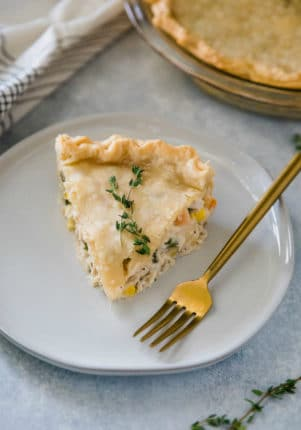 serving of chicken pot pie on a white plate with a gold fork