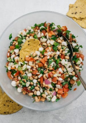 Cowboy Caviar mixed in a large bowl with a spoon and tortilla chip