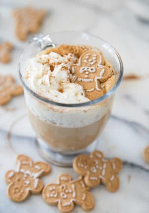 coffee with whipped cream and a gingerbread man cookie