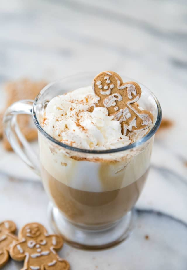 coffee in a glass mug with whipped cream and a gingerbread cookie