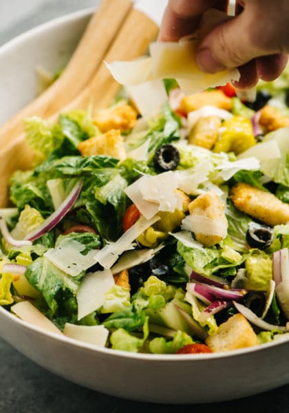 green salad in a large salad bowl with salad tongs