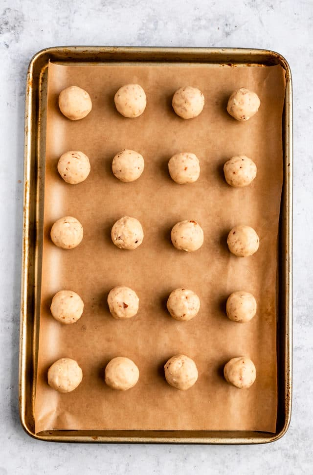 rolling balls of Mexican wedding cookie dough in balls and placing them on a baking sheet