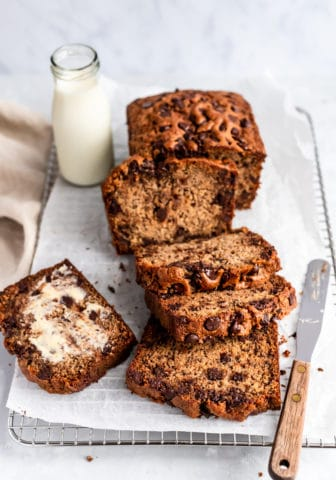 Chocolate Chip Banana Bread sliced on a bread board with a glass of milk