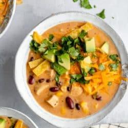 creamy chicken tortilla soup topped with cheese, avocado and fresh cilantro