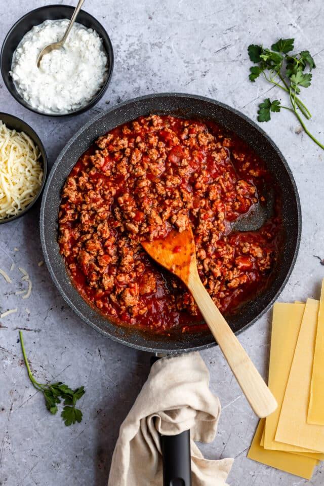 using a wooden spoon to stir ground turkey with marinara sauce