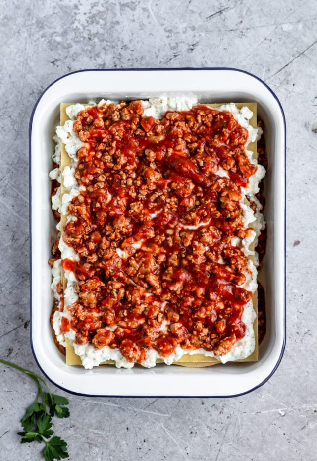 layering healthy lasagna in a white casserole dish