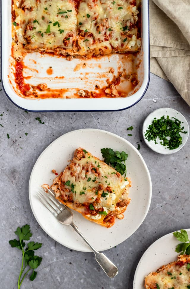 lasagna served on a white plate with fresh parsley
