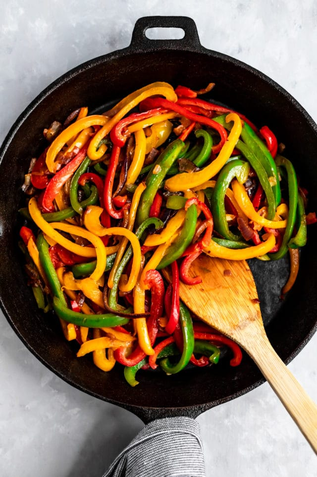 cooking bell peppers in an iron skillet