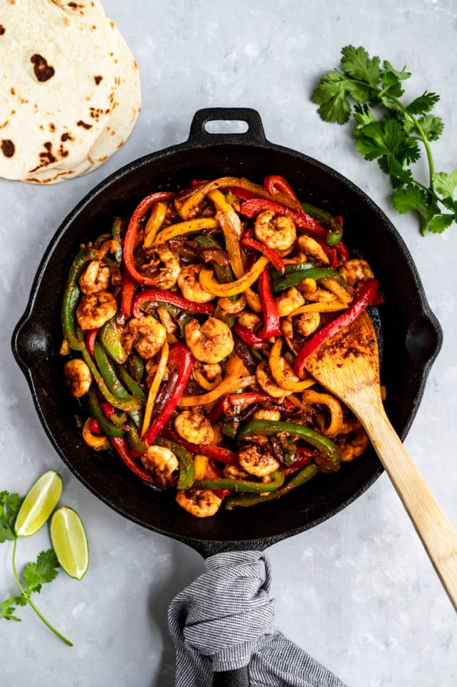 cooking shrimp, peppers and onion in an iron skillet