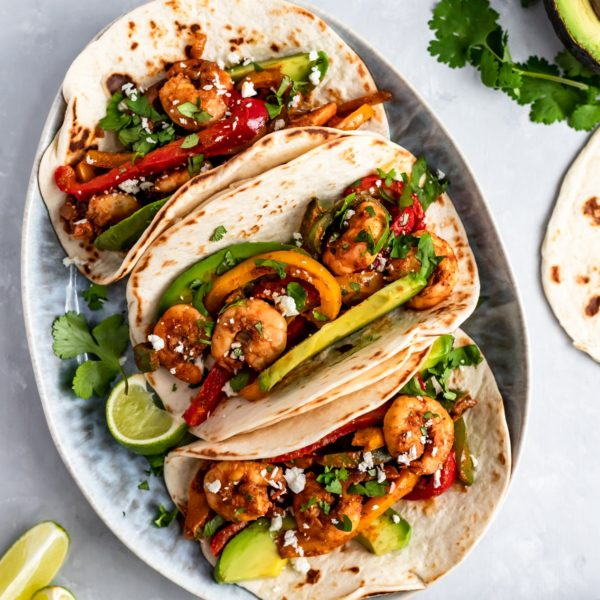 Shrimp Fajitas topped with avocado and serve with lime wedges