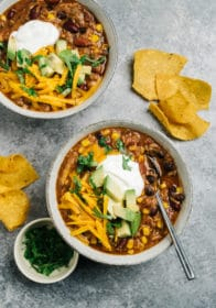 Chicken Taco Soup served in soup bowls with tortilla chips and topped with avocado, cheese and sour cream