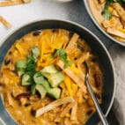 creamy tortilla soup in a bowl and topped with diced avocado, tortilla strips and cheese