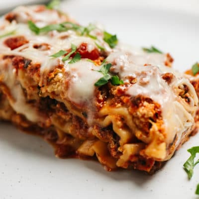 serving of lasagna on a white plate and topped with fresh parsley