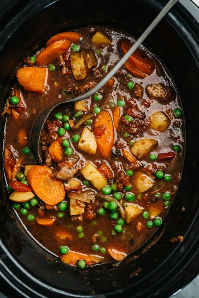 cooked vegetable beef soup in a slow cooker with a ladle