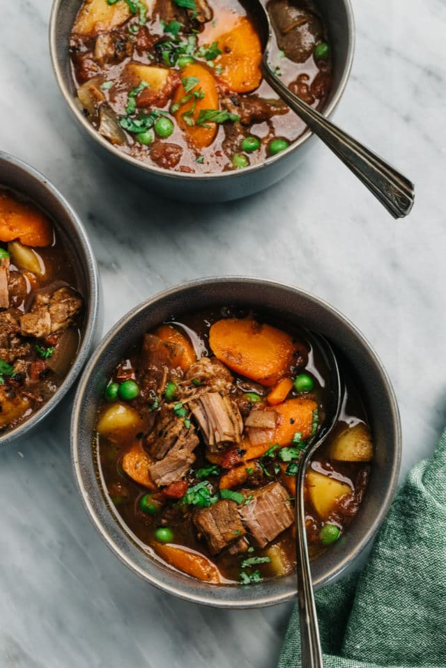 vegetable beef soup served in bowls with spoons