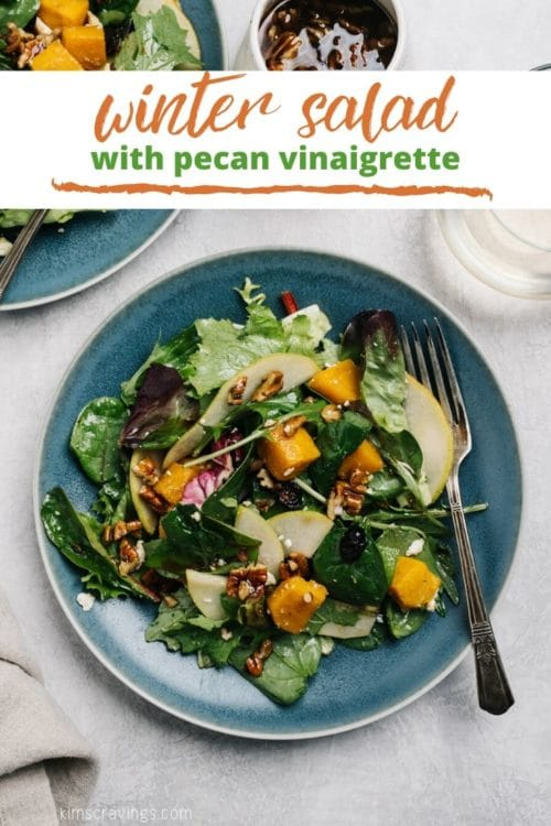 green salad with butternut squash and pecans served on a small blue plate