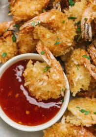 coconut shrimp dipped in cocktail sauce