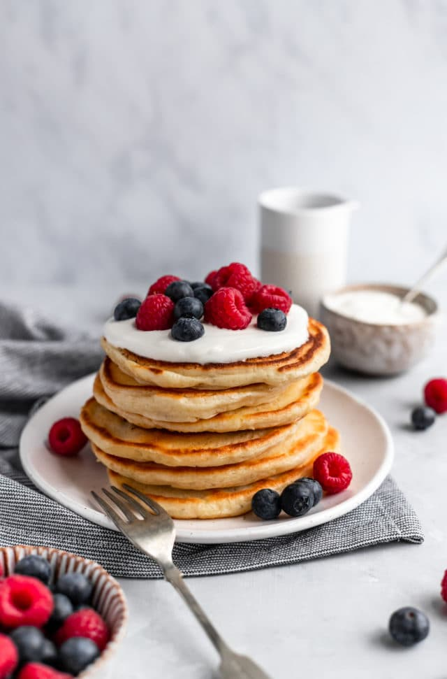fluffy pancakes stacked on a white plate and topped with berries
