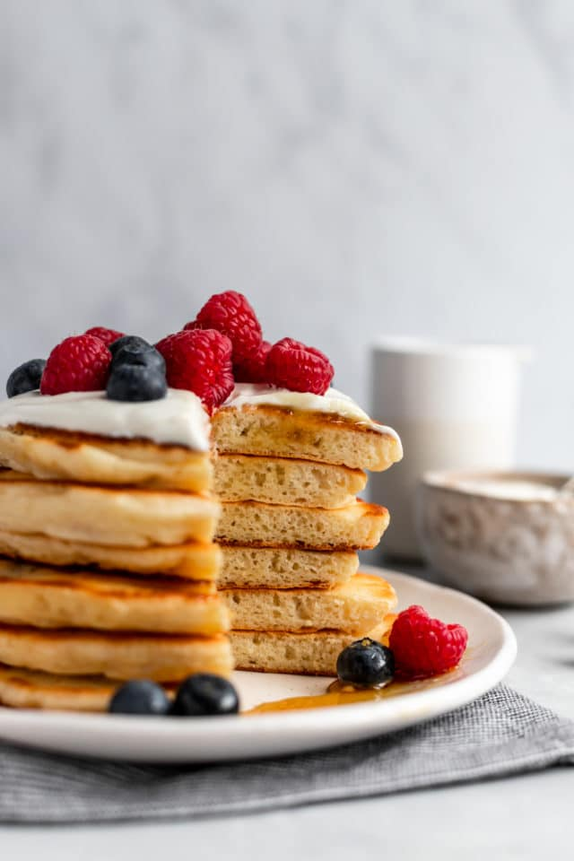 fluffy pancakes topped with yogurt and berries