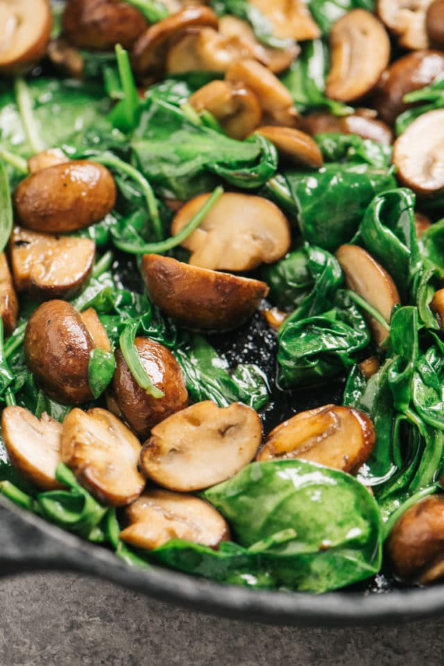 mushrooms and spinach sautéing in a skillet