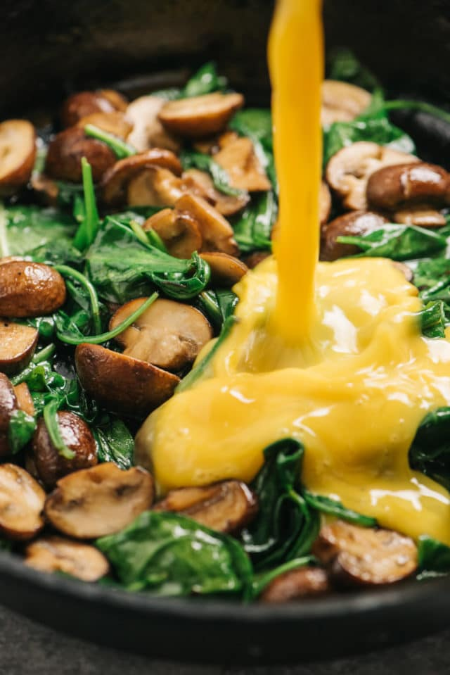 eggs being poured into a skillet with sautéed mushrooms and spinach