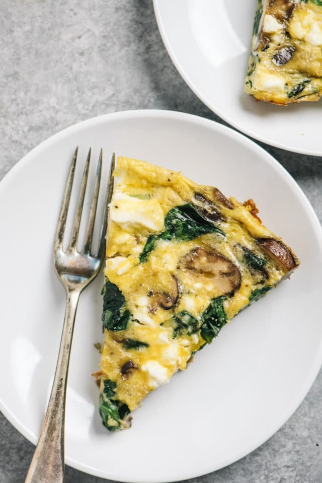 spinach and mushroom frittata on a white plate with a fork