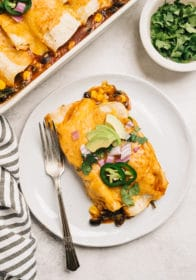 vegetarian enchiladas served on a white plate with a fork