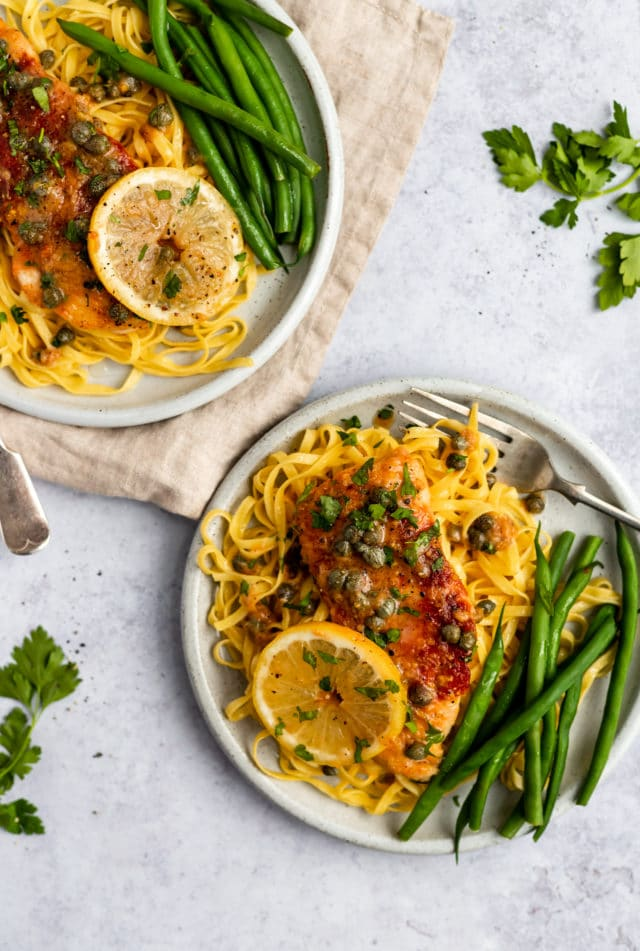 plates with chicken piccata over spaghetti with a lemon caper sauce
