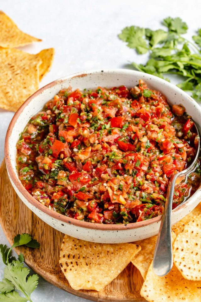 homemade salsa served in a small white bowl with a spoon