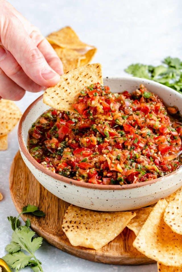 dipping a tortilla chip into a bowl of homemade salsa
