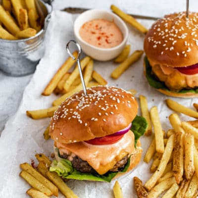 bacon cheese stuffed burgers dripping with burger sauce and served with French fries