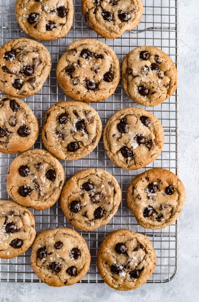 chewy chocolate chip cookies topped with course salt on a wire cooling rack