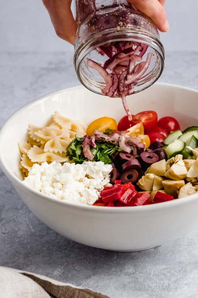 adding red onion and dressing to a large Greek pasta salad