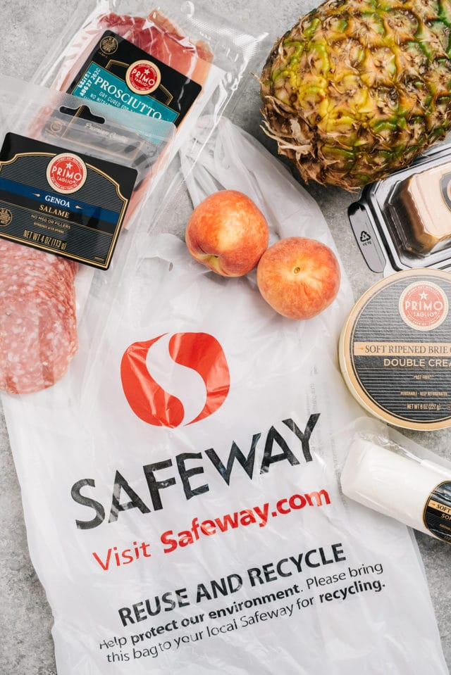 a Safeway shopping bag with meat, cheese and fruit