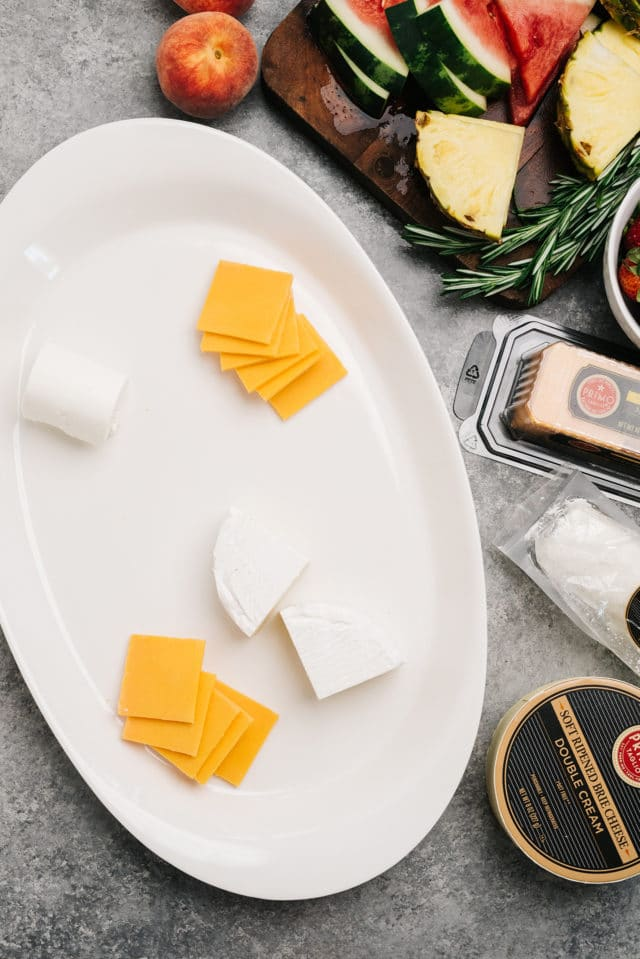 adding different types of cheese to a charcuterie board